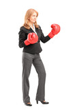 Mature businesswoman with red boxing gloves ready to fight