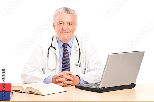 A mature doctor in his office posing