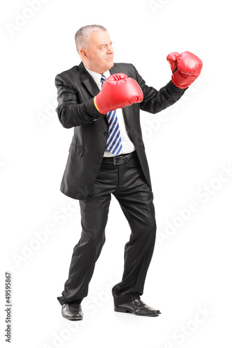 Mature businessman with red boxing gloves ready to fight