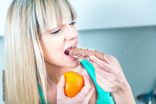beautiful woman biting a bar of chocolate