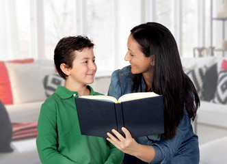 Mother teaching her child to read .