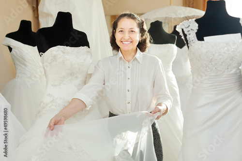 Woman shows bridal gown at shop