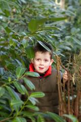 happy child peeking through a gap in the tree