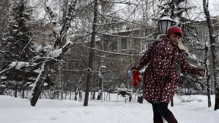 Young mother walking in a winter park with a sling