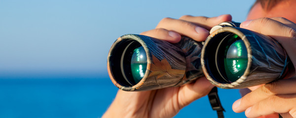 a man is looking to the binocular