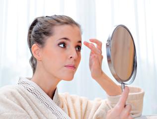 Beautiful woman in bathrobe looks at the mirror