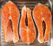 Three salmon steaks prepared for frying on grill pan
