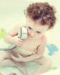 Baby playing in the bath making a phone call