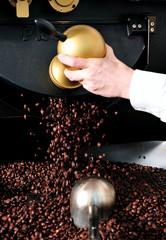 Kaffeebohnen fallen aus der Röstmaschine