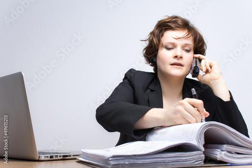 Junge Geschäftsfrau telefoniert am Arbeitsplatz