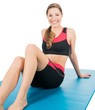 Beautifully smiling young woman on exercise mat