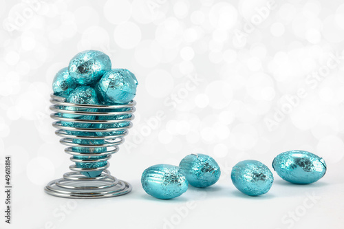 Blue foil Easter Eggs in wire eggcup.