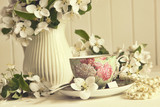 Fototapety Tea cup with apple blossoms on table