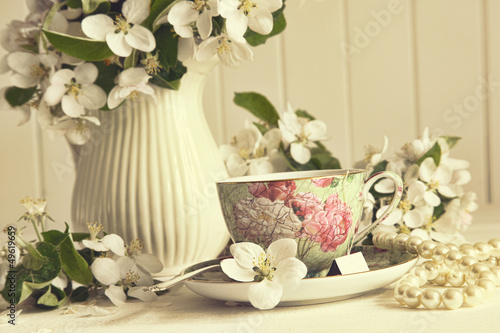 Tea cup with apple blossoms on table