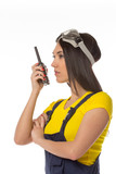 serious female construction worker talking with a walkie talkie poster