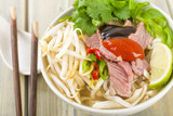 Pho Bo - Vietnamese rice noodle soup with beef, herbs and chili