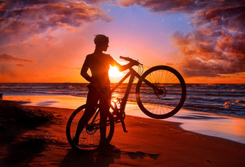 Woman with bicycle on the beach
