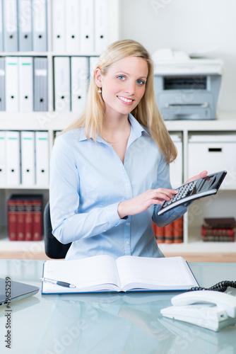 geschäftsfrau tippt auf einen taschenrechner