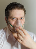 Portrait of young man with inhalator mask on the face