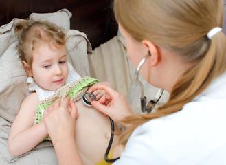 Female doctor examining little girl with stethoscope