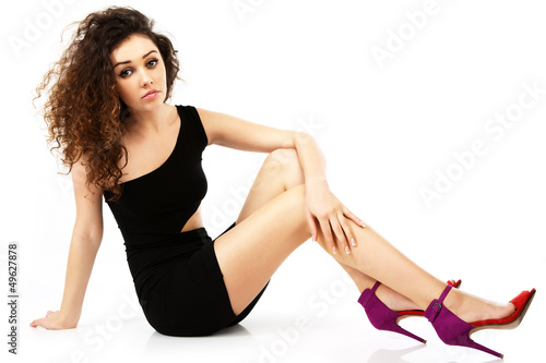A girl in a black dress in the studio on a white background