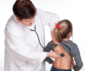 Senior doctor listening girl with stethoscope