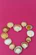 Heart made of shells on pink background