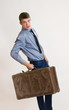Young businessman holding his old suitcase