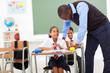 elementary teacher helping student in classroom