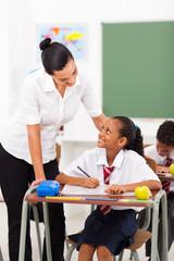 friendly female elementary school teacher talking to student