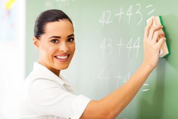 beautiful female elementary school teacher wiping chalkboard