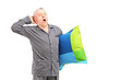 A sleepy mature man in pajamas holding a pillow and yawning
