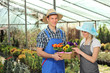 Female and male gardeners with a basket full of flower pots in a