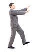 Full length portrait of a young man in pajamas sleepwalking