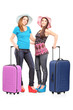 Full length portrait of two teenagers with suitcases ready for j