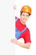 Young construction worker with helmet posing behind a panel