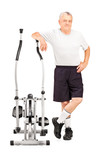Mature athlete standing next to a cross trainer machine
