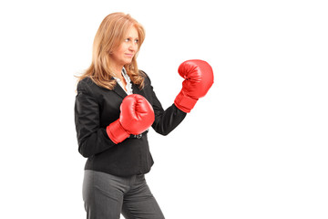 A mature businesswoman with red boxing gloves ready to fight