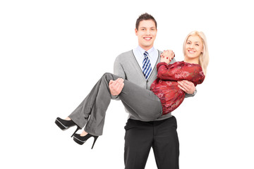 Happy young man carrying his girlfriend in his arms