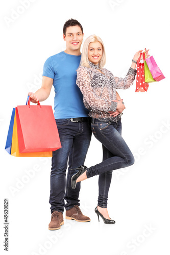 Full length portrait of a happy young couple holding shopping ba