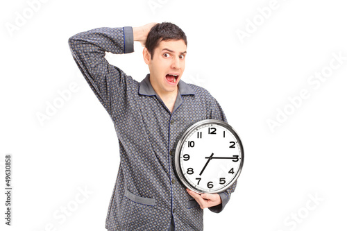 Shocked male in pijamas holding an alarm clock