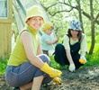women with child works at vegetables garden