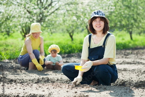 women with child works at vegetables garden