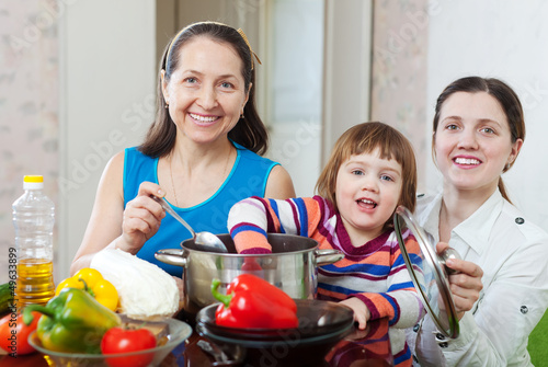 Mature woman and adult daughter with girl cook lunch