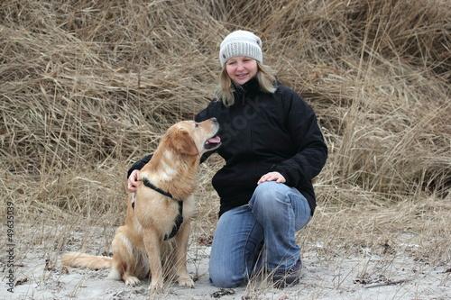 junge Frau mit Golden Retriever am Strand