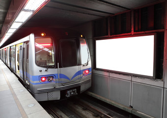train at metro station with billboard