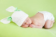 Funny sleeping newborn baby girl over green background