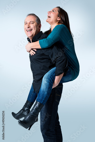 Happy young man giving a piggyback ride to her wife