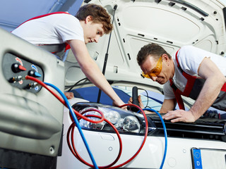 Two car mechanics check the air handling unit of a car