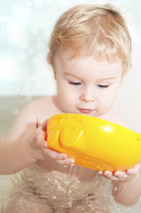 The beautiful child, bathing with toys